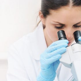 40809853 - young woman medical researcher looking through microscope in laboratory medicine concept